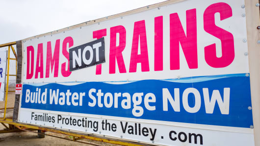 Sign in the San Joaquin Valley of California protesting water politics and the construction of high speed rail lines, with text reading Dams Not Trains, Build Water Storage NOW, along the Interstate 5 freeway, created by political group Families Protecting the Valley, December 9, 2018.