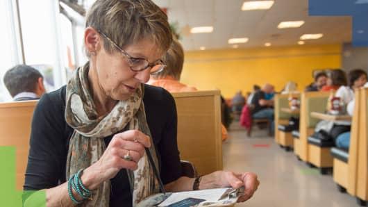 Boomer Woman paying bill at restaurant