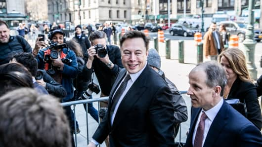 Elon Musk, chief executive officer of Tesla Inc., center, arrives at federal court in New York, on Thursday, April 4, 2019.