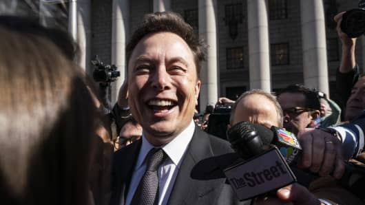 Elon Musk, chief executive officer of Tesla Inc., smiles while speaking to members of the media outside federal court in New York, U.S., on Thursday, April 4, 2019.