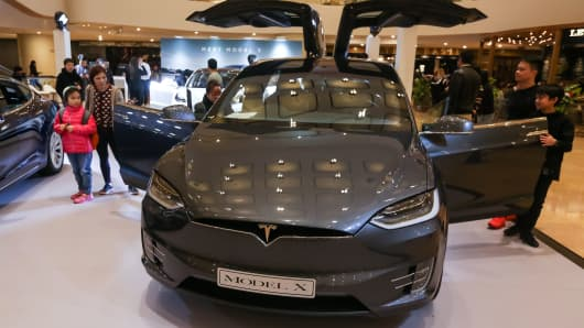 People look at a Tesla Model X displayed at a shopping mall in Hong Kong on March 10, 2019