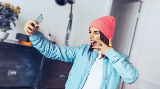 french stylish teenage girl posing for selfie indoor