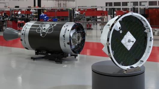 "Rocket Lab's ""Photon"" satellite platform, on the right, is shown at the company's factory alongside an upper stage of the Electron rocket."