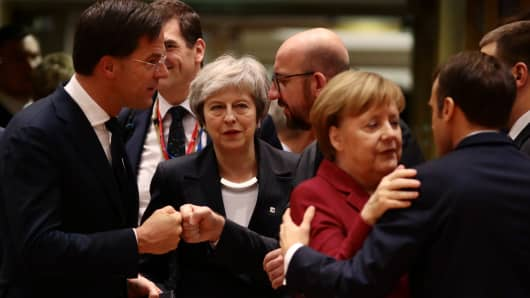Britain's Prime Minister Theresa May (C) looks on as (L-R) Netherlands' Prime Minister Mark Rutte, Belgian Prime Minister Charles Michel, German Chancellor Angela Merkel and France's President Emmanuel Macron greet each other at the European Council during the start of the two day EU summit on December 13, 2018.