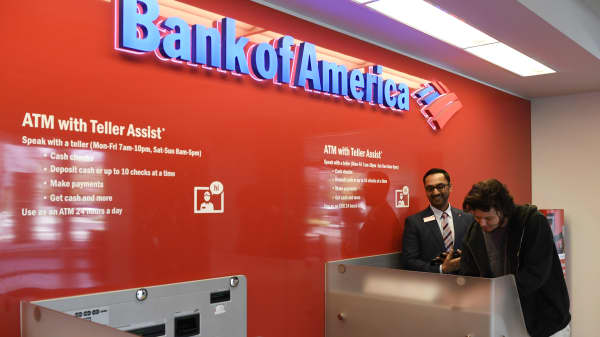 A Bank of America financial manager shows a customer how to use the ATM with Teller Assist station in Cherry Creek.
