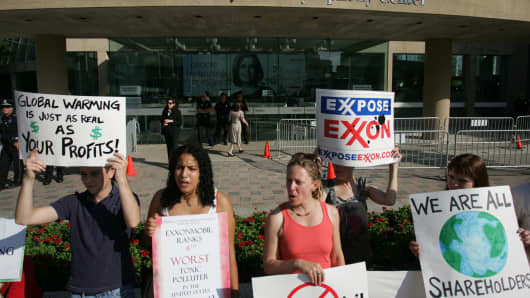 Protesters hold signs outside an Exxon Mobil annual shareholders meeting. In 2017, Vanguard Group joined other big fund companies including BlackRock and State Street Global Advisors that voted to require the oil giant to produce a climate change report.