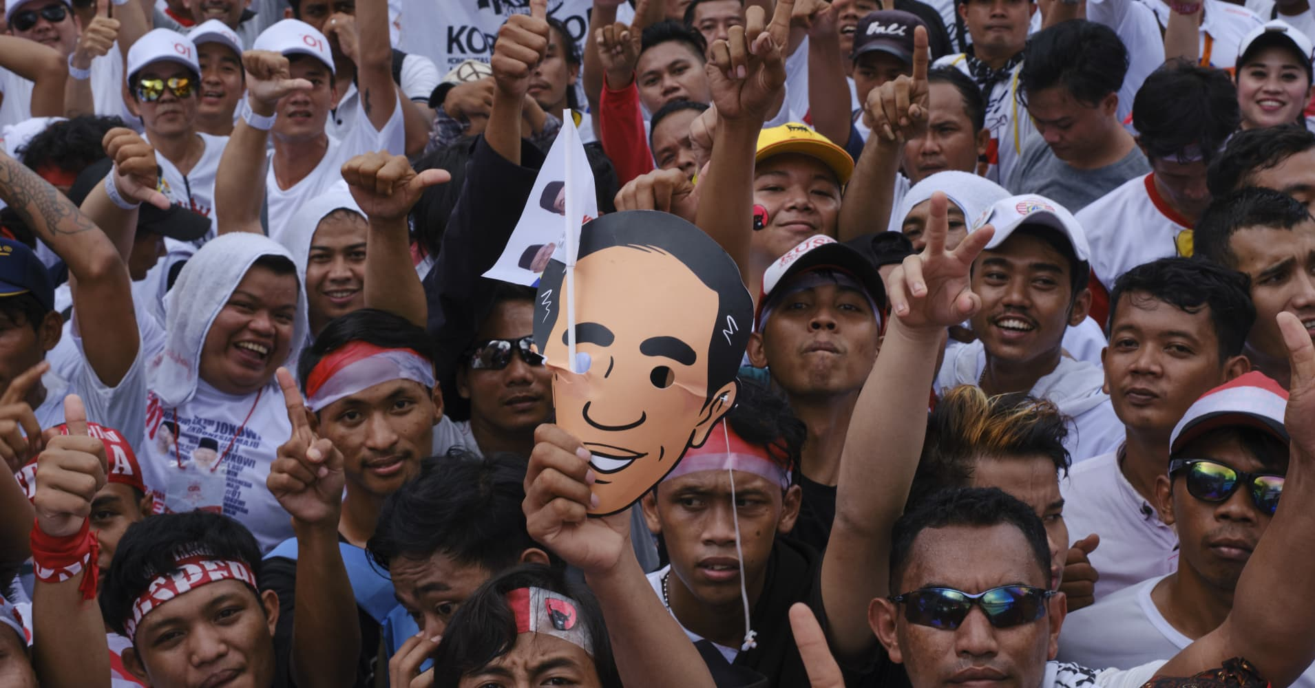 A crowd holding a a mask with a cartoon image of Indonesian President Joko Widodo at a political rally in Jakarta, Indonesia.
