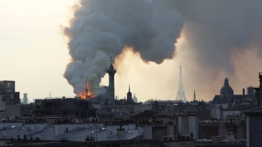 A huge column of smoke stands above one of the world's most famous landmarks - Notre-Dame Cathedral in Paris.