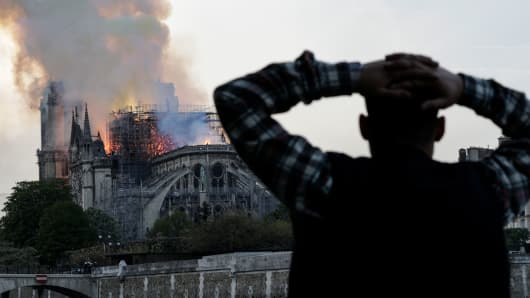 A particular person watches the landmark Notre-Dame Cathedral burn, engulfed in flames, in central Paris on April 15, 2019.