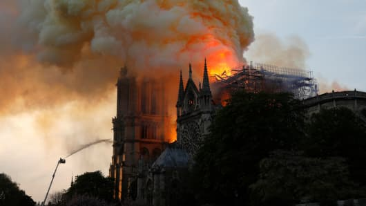 A firefighter uses a hose to douse flames and smoke billowing from the roof at Notre-Dame Cathedral in Paris on April 15, 2019.
