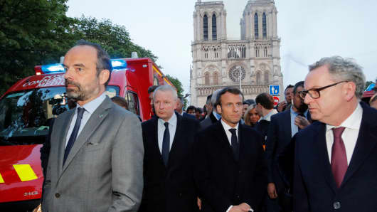 French Prime Minister Edouard Philippe (L), and French President Emmanuel Macron (3rd L) gather in near the entrance of the Notre-Dame de Paris Cathedral in Paris, as flames engulf its roof.