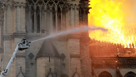 A firefighter is viewed combating the flames at Notre-Dame Cathedral