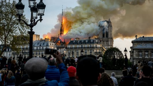 People watch the landmark Notre-Dame Cathedral burning in central Paris on April 15, 2019- A fire broke out at the landmark Notre-Dame Cathedral in central Paris, potentially involving renovation works being carried out at the site, the fire service said. (Photo by Nicolas Liponne/NurPhoto via Getty Images)