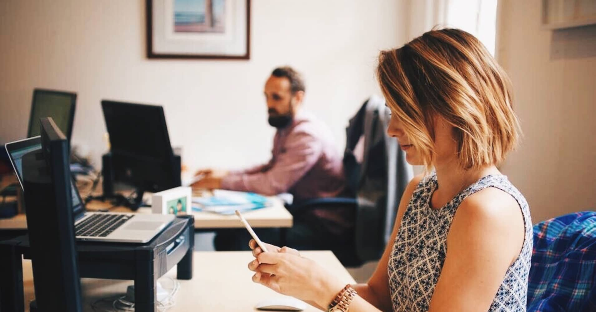 A woman and man work at their desks.
