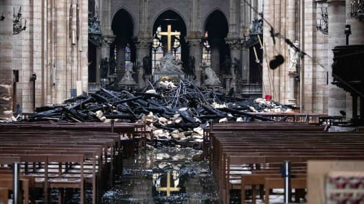 Fallen debris from the burnt out roof structure sits near the altar inside Notre Dame Cathedral in Paris, France, on Tuesday, April 16, 2019.