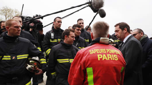French Interior Minister Christophe Castaner (2-R), French Junior Interior Minister Laurent Nunez (R) meet with Paris fire brigade commander general Jean-Claude Gallet (back) and fire fighters outside Notre-Dame-de Paris in the aftermath of a fire that devastated the cathedral in Paris,on April 16, 2019.