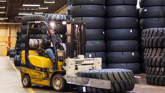 An employee uses a forklift to move large construction tires at the Titan Tire Corp. warehouse in Bryan, Ohio.