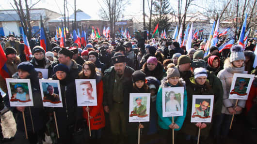 People hold portraits as they take part in a rally in memory of the victims of the Donbass military conflict.