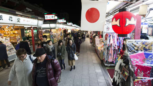 A Japanese flag is displayed as shoppers and pedestrians walk past stores at a shopping street in Tokyo, Japan, on Wednesday, Nov. 23, 2016.