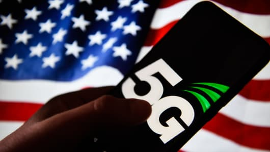 A 5G attach is seen on an android cell phone with United States of The United States flag on the background.