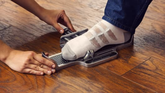 A shopper's foot is measured using a brannock device.