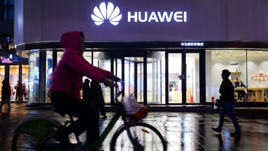 Една жена минава покрай магазин Huawei в Шенянг, Китай.