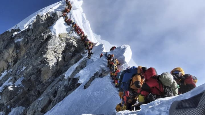 In this photo made on May 22, 2019, a long queue of mountain climbers line a path on Mount Everest.