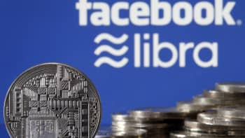 A visual representation of a cryptocurrency coin on display in front of the logos for Facebook and Libra.