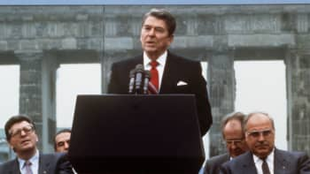 "Former US President Ronald Reagan (center) gives a speech in front of the Berlin wall at the Brandenburg gate in Berlin, Germany, June 12, 1987. German chancellor Helmut Kohl and then president of the parliament Philipp Jenninger can be seen next to him. Reagan voiced the famous words ""Mr. Gorbachev, tear down this wall."""