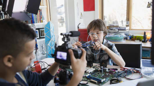 Boys videotaping circuit board assembly in bedroom