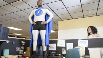 A black businessman office super hero stands on his cubicle desk ready for action.