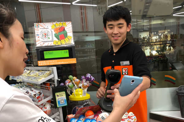 A 711 employee accepts a mobile payment from a customer in Shenzhen, China