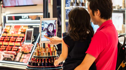 A father and daughter play with a digital tablet at an Estée Lauder store in Shanghai.