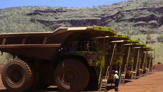 An employee stands next to a fleet of Caterpillar 793F autonomous haul trucks at the Kings mine site at Fortescue Metals Group Ltd.'s Solomon mining hub in the Pilbara region, Western Australia