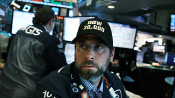 """Traders wear """"DOW 28,000"""" hats on the floor of the New York Stock Exchange (NYSE) on November 15, 2019 in New York City. As trade talks with China show some progress, the Dow Jones Industrial Average rose 222 points to close above 28, 000 for a new record."""